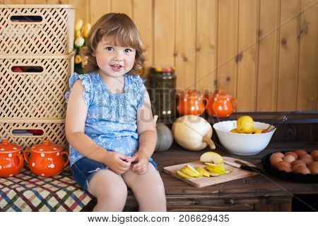 Cute toddler smiling kid in the rustic kitchen indoors. Baking sweet apple cake and having fun. Flour dirty hands apples eggs and backing dish. Homemade food. Mother's little helper.