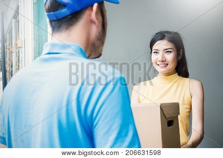 Asian woman accepting receive a delivery of boxes from delivery asian man sign and receive delivery concept