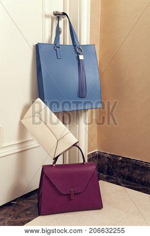 Beautiful luxury leather women's blue, beige and purple bags weighs on the door handle, lie on the floor