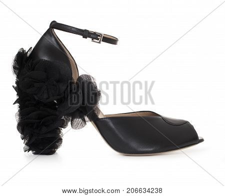 Beautiful female luxurious leather black shoe, high-heeled, with a décor of fabric and leather, on a white background, side view