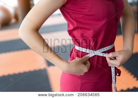 Young woman waist measuring using measure tape for checking weight calories slim body Closeup at gym indoor and fitness exercise