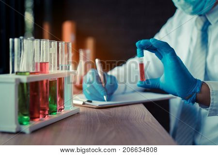 Scientist man with glasses working research and conducts experiments by synthesis compounds in laboratory and the test tube lecture results