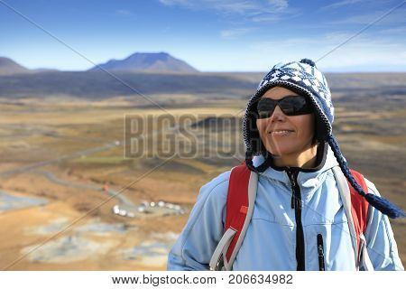 Portrait of a woman on the background of steaming fumaroles at Hverir geothermal area in north Iceland