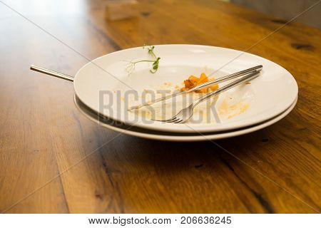 Empty plate left after dinner, lying on a wooden table