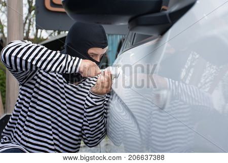 The man robber with a balaclava on his head trying to break into the car. He uses a screwdriver/Criminal and car thief concept
