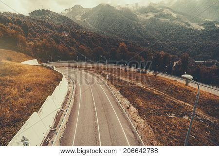 Beautiful autumn scenery with mountain road bending to the tunnel hazy hill ridge in background multiple pillars traffic signs dry grass safety fence; Estosadok district Sochi Russia