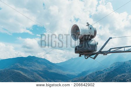 Close-up view of snow emitter fan device placed on crane and stunning autumn mountain landscape in the background; copy space zone for text your logo or advertising message