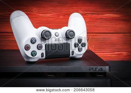 Sankt-Petersburg Russia September 24 2017: Sony PlayStation 4 Slim 1Tb revision and dualshock game controller on the red wood background