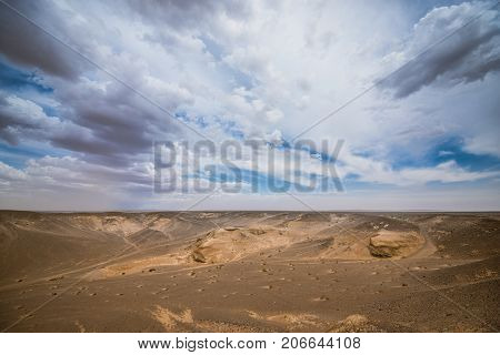 beautiful landscape of sunlit sand dunes with cloudy sky on background