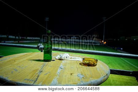 Empty beer bottle and ashtray  on a table