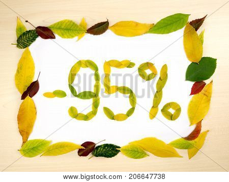 Word 95 percent made of autumn leaves inside of frame of autumn leaves on wood background. Ninety five percent sale. Autumn sale template