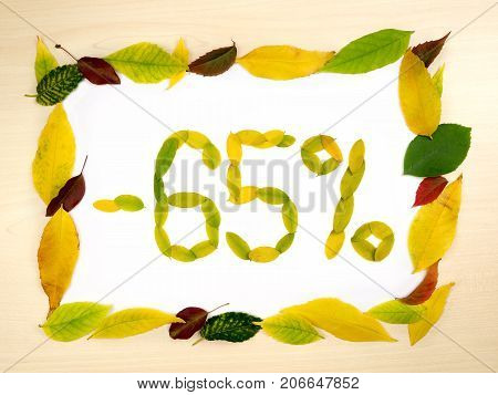Word 65 percent made of autumn leaves inside of frame of autumn leaves on wood background. Sixty five percent sale. Autumn sale template