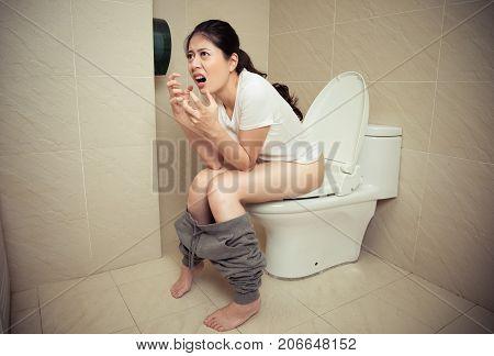 Pretty Woman Sitting On Toilet In Bathroom