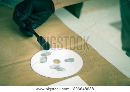 forensic hand in glove brushing latent fingrprints evidence by magnetic powder on compact disc with copy space in cenematic tone