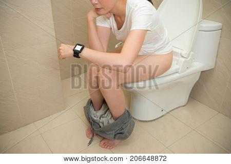 Elegant Smiling Girl Sitting On Bathroom Toilet