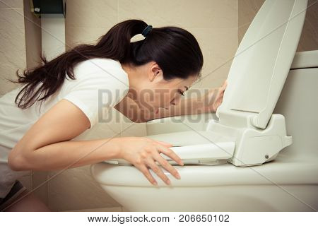 Closeup Of Young Pretty Woman Vomiting Into Toilet
