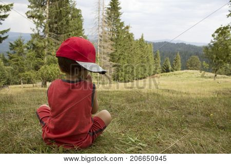 Small Boy in red cap and red t-shirt sit thinking on the grass hill in the mountain. autumn day.  back view. concept of travel and childhood.