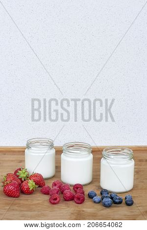 Three glass jars with yogurt and variation of berries - mock up template