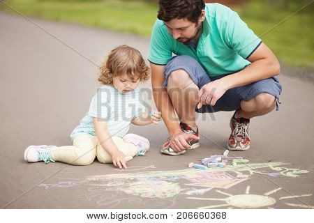 Caring father happy family. Drawing with color chalk. Sunny summer days. Happy childhood. Preschooler leisure time. Kids spending time with parents. Artistic talented kids. Colorful chalk drawing. Father and daughter relationshionships.