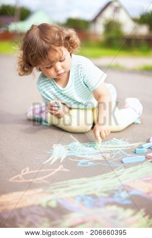 Sunny and warm summer days and happy chilhood. Cute little girl drawing with chalk crayons at the asphalt. Child having fun alone. Spending time without parents and adults. Kids drawings: sun house flowers.