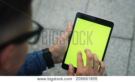 Close Up Shot Of Attractive Man Using Tablet With Green Screen While Sitting In The City. Chroma Key