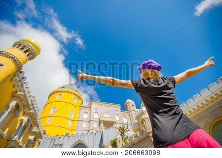 Travel in Europe. Prospective view of happy woman with open arms at Pena Palace, Unesco Heritage and one of Seven Wonders of Portugal in Sintra.Pena Castle on blurred background. Female tourist enjoys