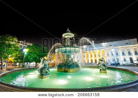 Lisbon downtown, Portugal, Europe, Baixa District. Urban scene by night. Baroque fountain on popular Praca Dom Pedro IV or Rossio Square. The National Theater D. Maria on background.