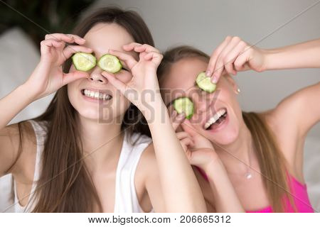 Two young smiling girlfriends being silly, putting cucumbers on their eyes and making funny faces. Best friends having fun, using natural product for beauty routine. Close up, facing camera portrait.