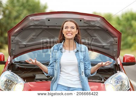 Angry young woman near broken car