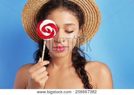 Beautiful young woman with lollypop on color background