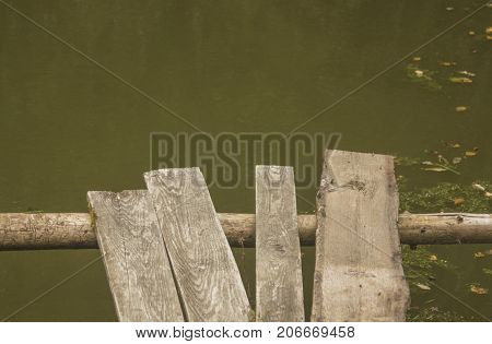 Wooden ramshackle walkway over old green pond
