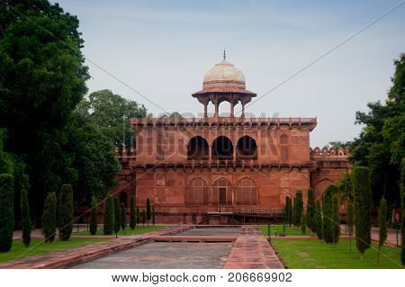 Sand stone building with arched doorways and a dome situated in a beautiful garden. The beauty and perfection is typical of mughal architecture. Many such buildings are part of the Taj Mahal complex