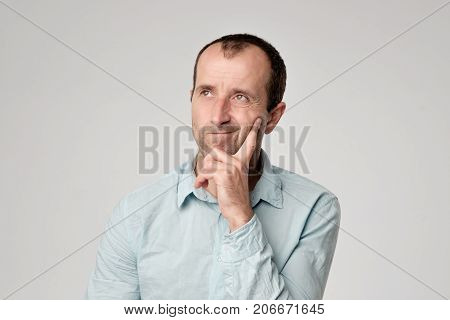 Caucasian man in blue t-shirt looking down with skeptical emotion on face. He is unsure in desicions