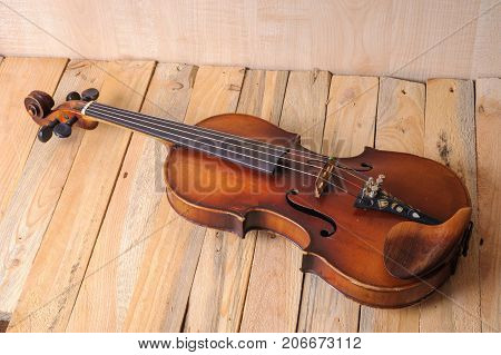 one violin image .old brown stringed wooden instrument isolated on the wood background