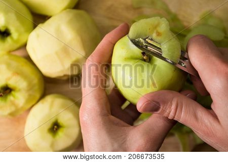 Female Hands Peeling Skin Off Of Green Apple Using A Paring Knife