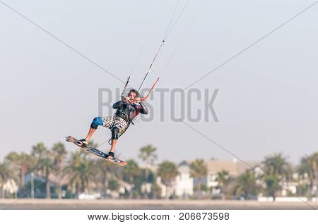 WALVIS BAY NAMIBIA - JULY 2 2017: An unidentified airborne kite surfer on the lagoon at Walvis Bay in the Namib Desert on the Atlantic Coast of Namibia
