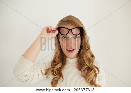 This is unbelievable. Shock surprise and astonishment concept. Attractive young lady with curly fair hair raising her trendy spectacles in black frame and opening mouth having surprised look