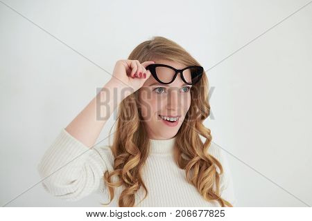 Horizontal shot of fascinated or astonished young European female wearing turtle neck holding stylish eyeglasses at her head and looking ahead of her with amazed shocked expression. Human emotions