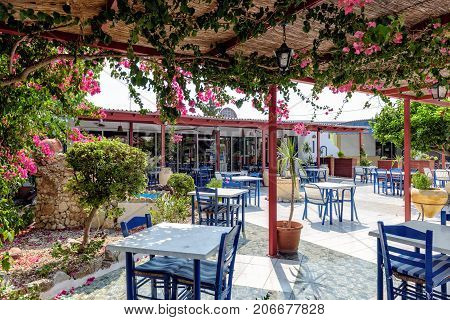 RHODES, GREECE - AUGUST 2017: Traditional Greek tavern with blue tables and chairs on Rhodes island.