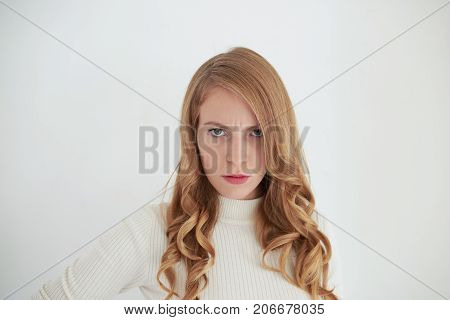 Picture of serious angry adult woman with blue eyes and curly hair frowning feeling furious avenging herself on husband for cheating on her. Negative human emotions reaction feelings and attitude