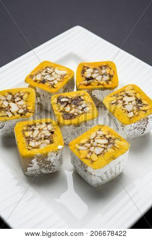 poster of stock photo of sweet Mawa burfi for diwal wrapped with silver foili, selective focus