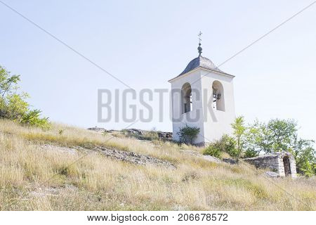 A temple on the slope near green tree and golden grass in sunny day. Orthodox church with cross on the bell tower. View from the bottom up.  Concept of credo and religion.
