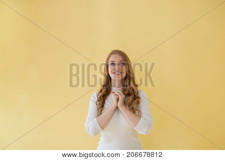 Superstitious hopeful young woman with wavy hair smiling cheerfully holding clasped hands in front of her while praying before exams or job interview. Positive cute woman expressing gratitude