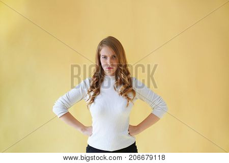 Portrait of fed up grumpy adult Caucasian housewife keeping hands on waist frowning eyebrows annoyed with misbehavior of her spoiled child. Irritated young businesswoman loosing her temper