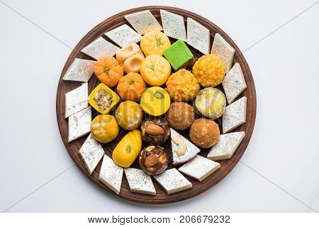 Stock photo of Indian sweets served in silver or wooden plate. variety of Peda, burfi, laddu in decorative plate, selective focus poster