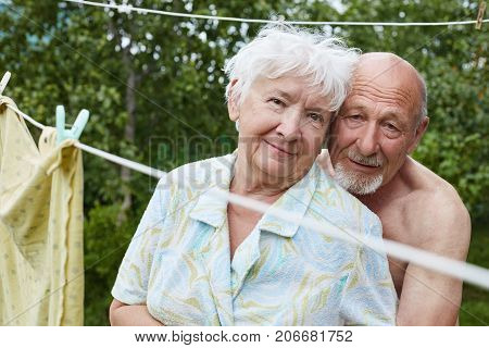 Authentic shot of aging couple in the Russian villiage yard. Bolded tanned man with grey beard hugs his partner with love and devotion woman smiling with tenderness.Love and family concept.