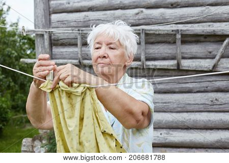 Authentic outdoors portrait of charming grey haired Caucasian old grey haired woman. Grandmother is hanging shirt to dry on a clothesline against bathhouse background. Village lifestyle rural scene.