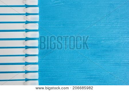 White Plastic Templates For Nail Polish Varnish. On A Blue Wooden Table.