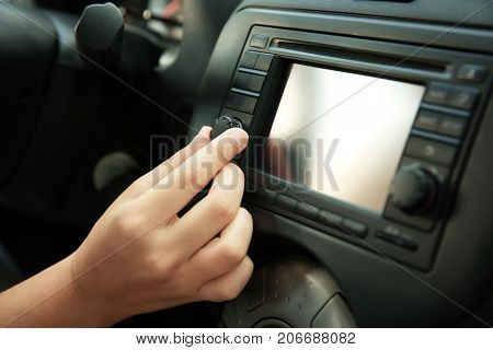 Woman tuning radio in car, closeup