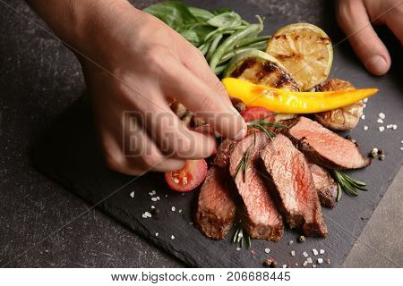 Chef decorating tasty juicy meat on slate plate